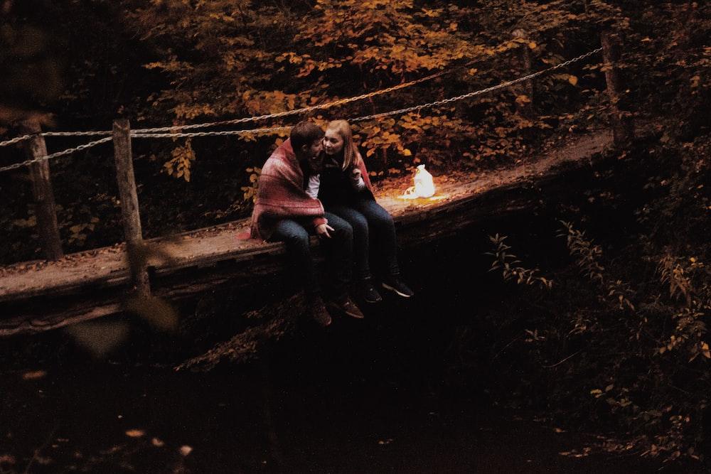 couple sitting on bridge