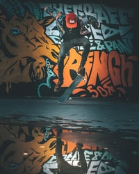 person performing skateboard trick near wall with graffiti