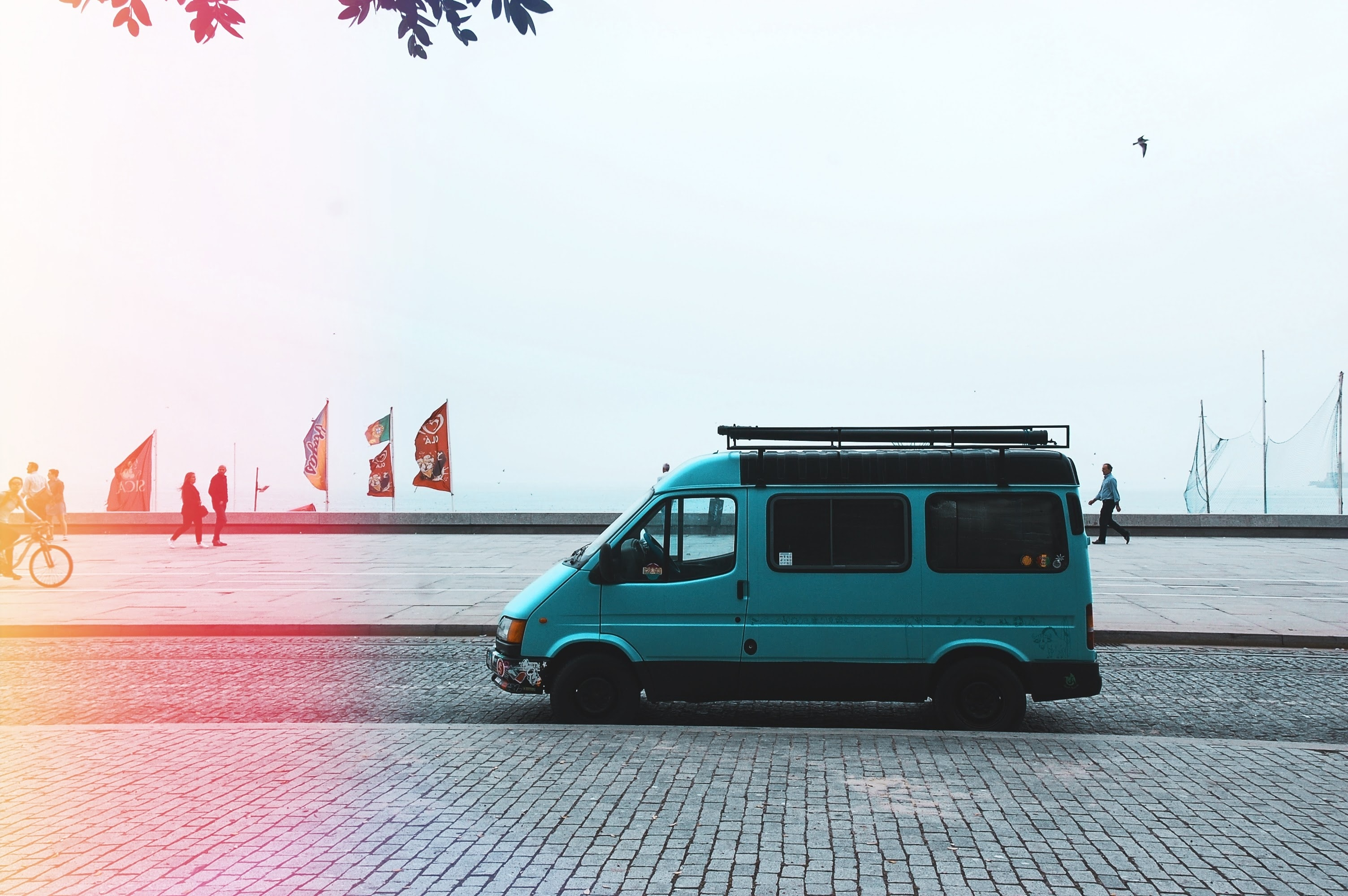 teal van on gray asphalt road