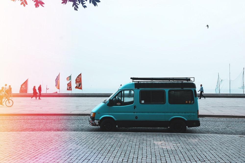 teal van on gray asphalt road