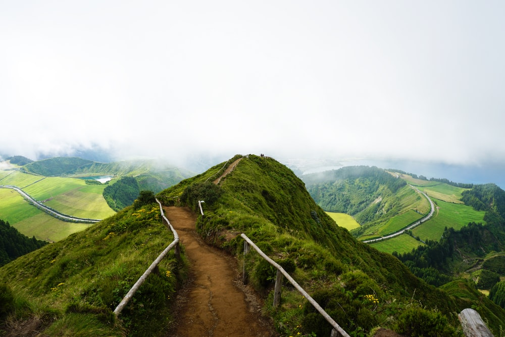 pathway in the middle of hill under cloudy sky