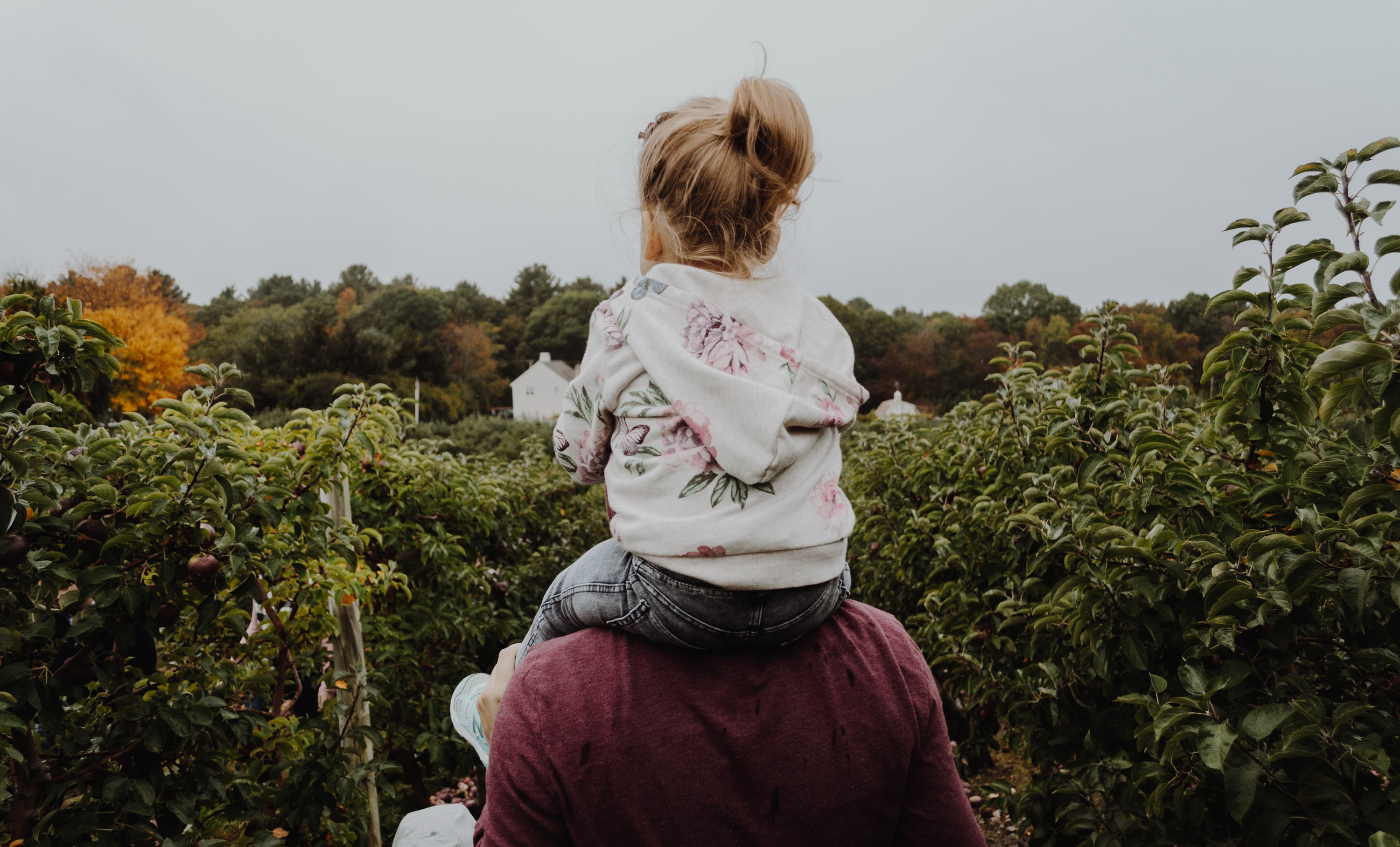 photo of girl riding on person shoulder