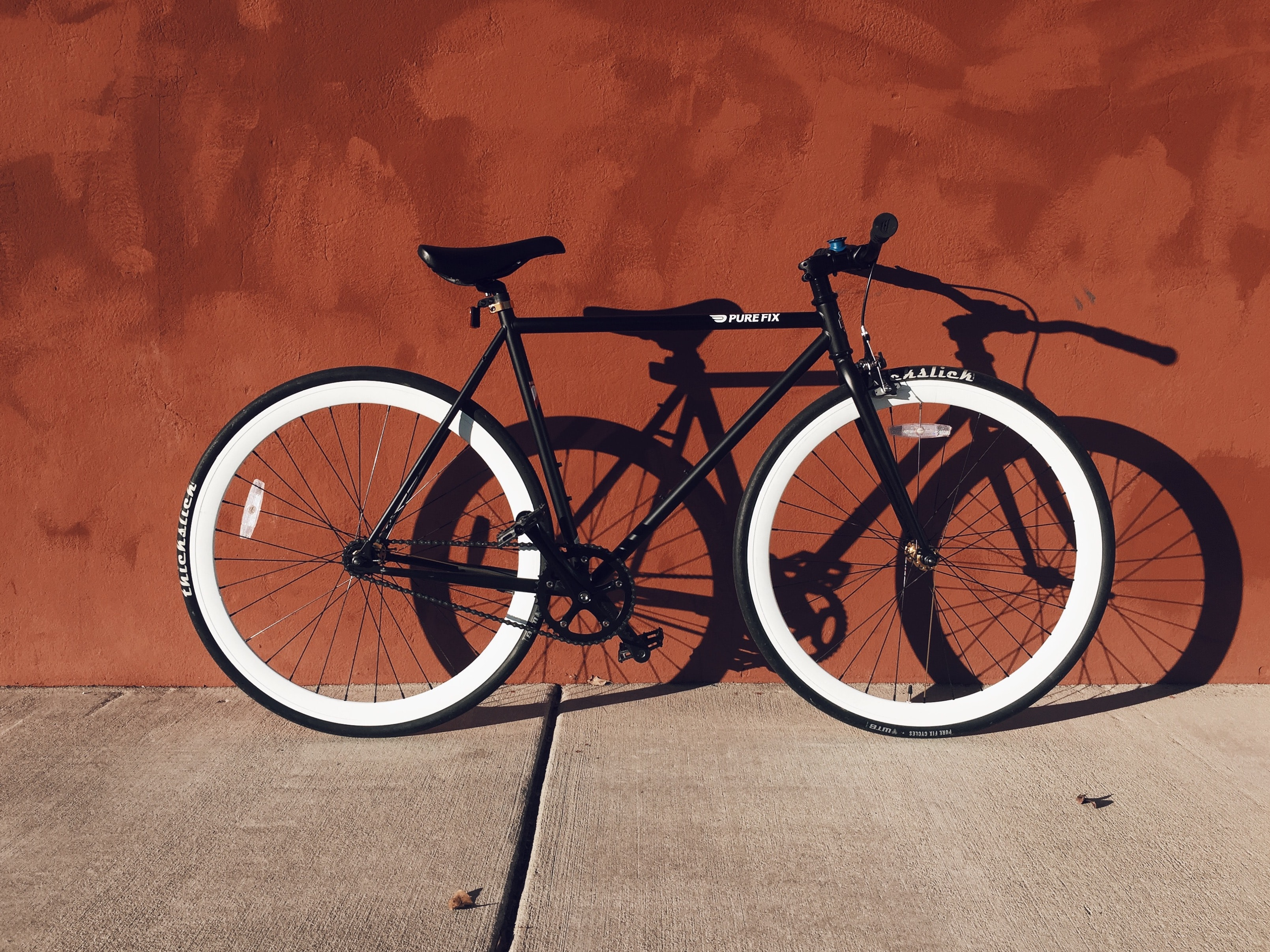 black and white mountain bicycle near brown wall