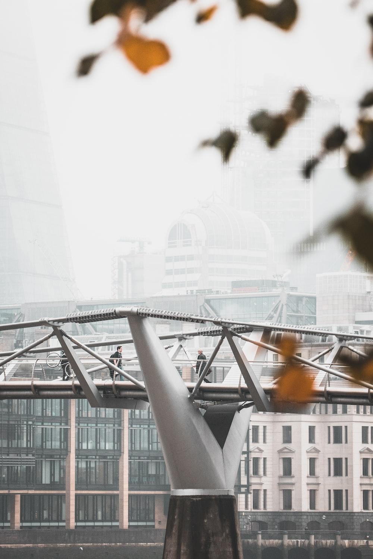 photo of man walking on gray bridge