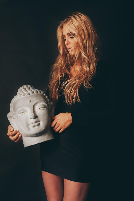 woman holding Gautama Buddha head statue