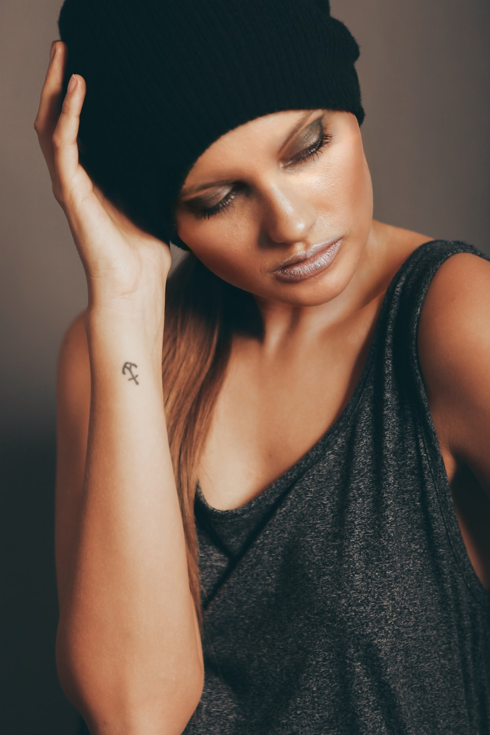 woman wearing black tank top and black knit cap holding head