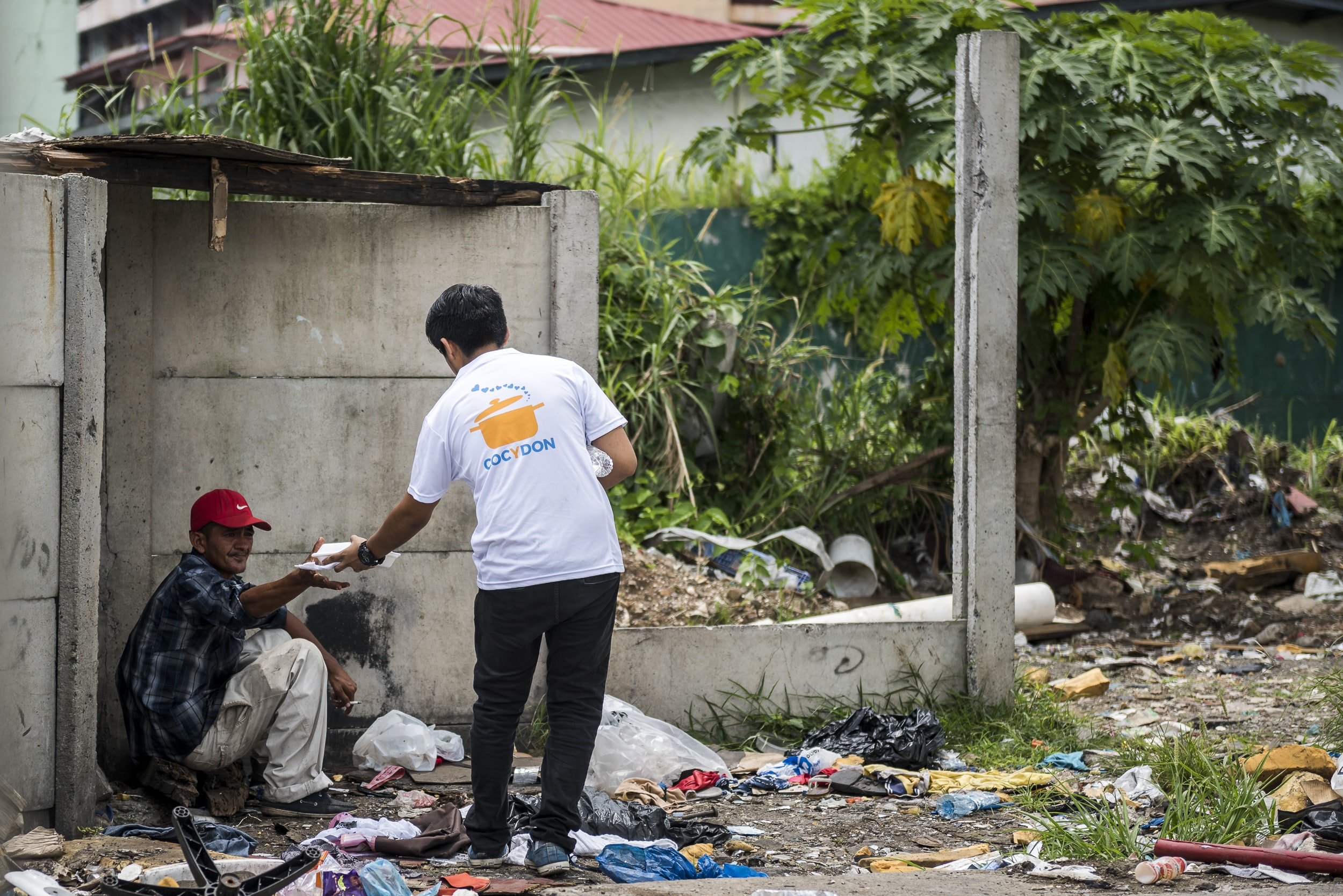 man giving food on man sitting on corner of wall