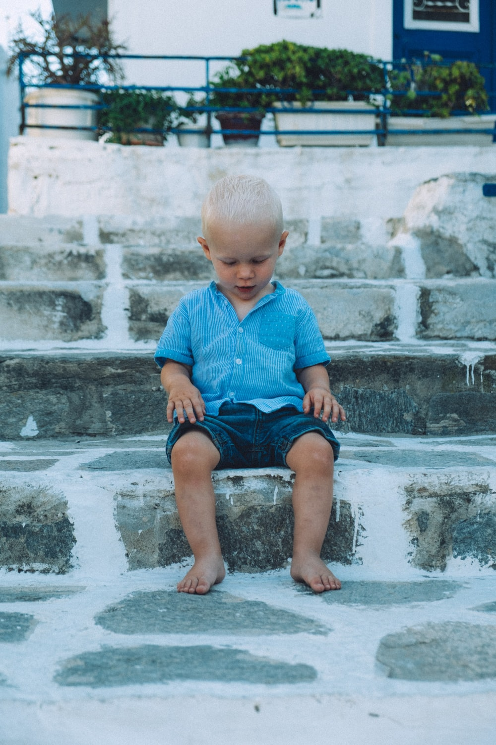 boy sitting on gray concrete stair