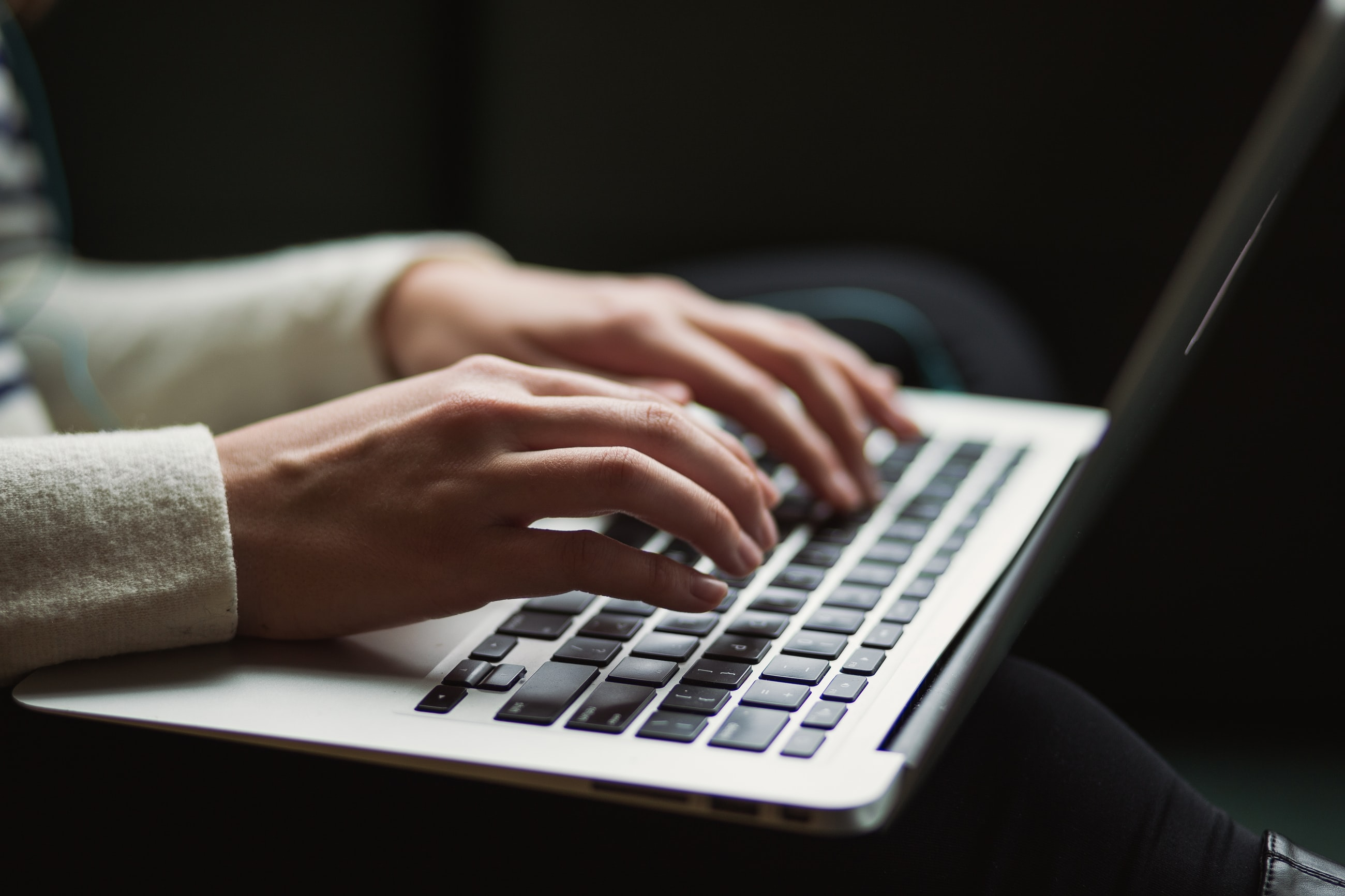 Hands typing on an Apple Laptop