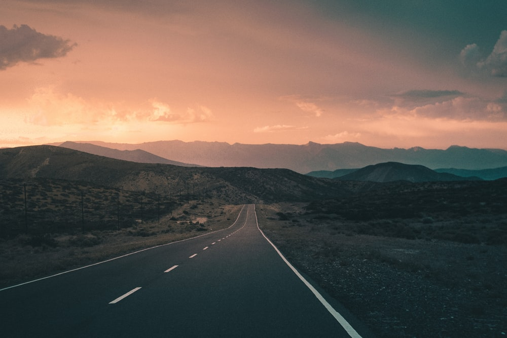 empty road pavement near the mountain photography