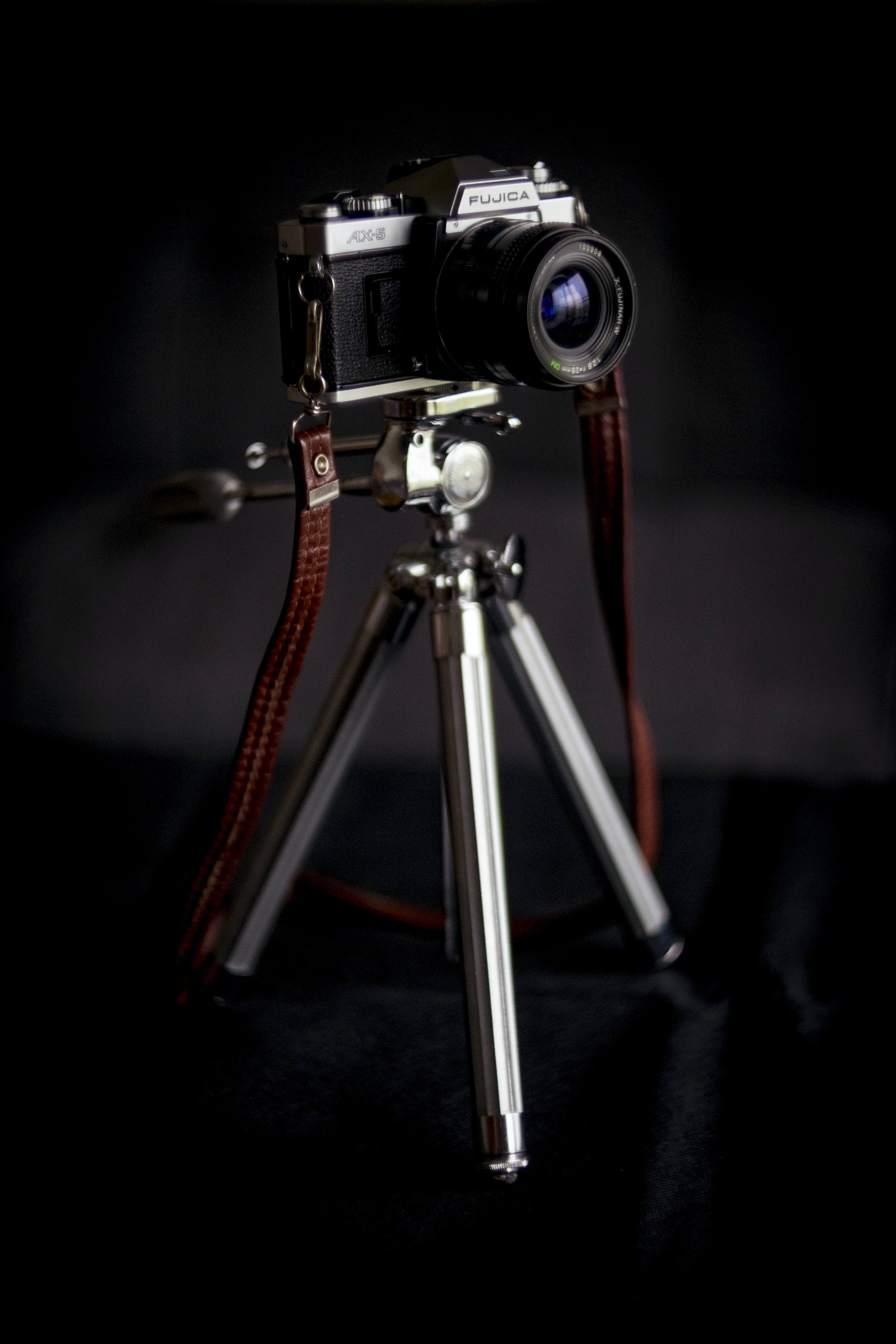 black and silver DSLR camera with tripod