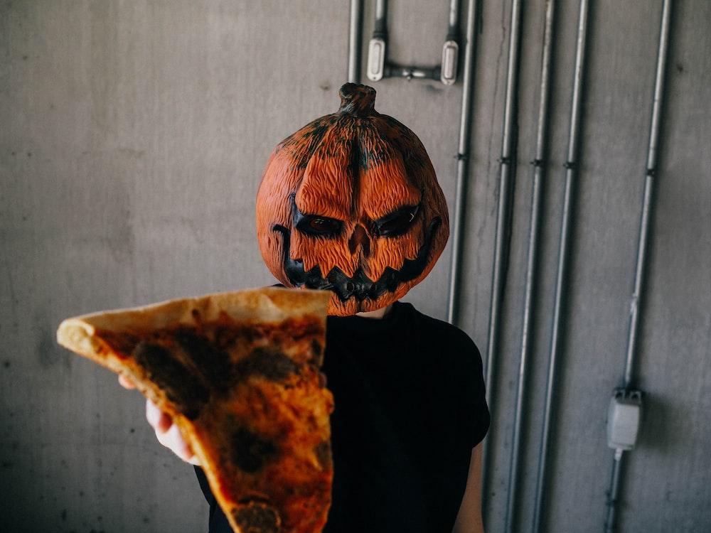 man wearing Jack'-o-lantern mask holding sliced pizza