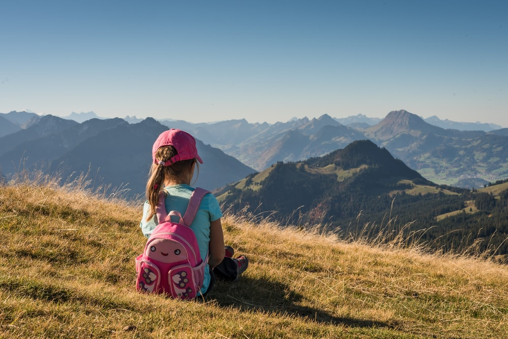 girl sitting on hill
