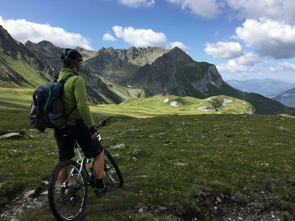 man riding bicycle on top of mountain