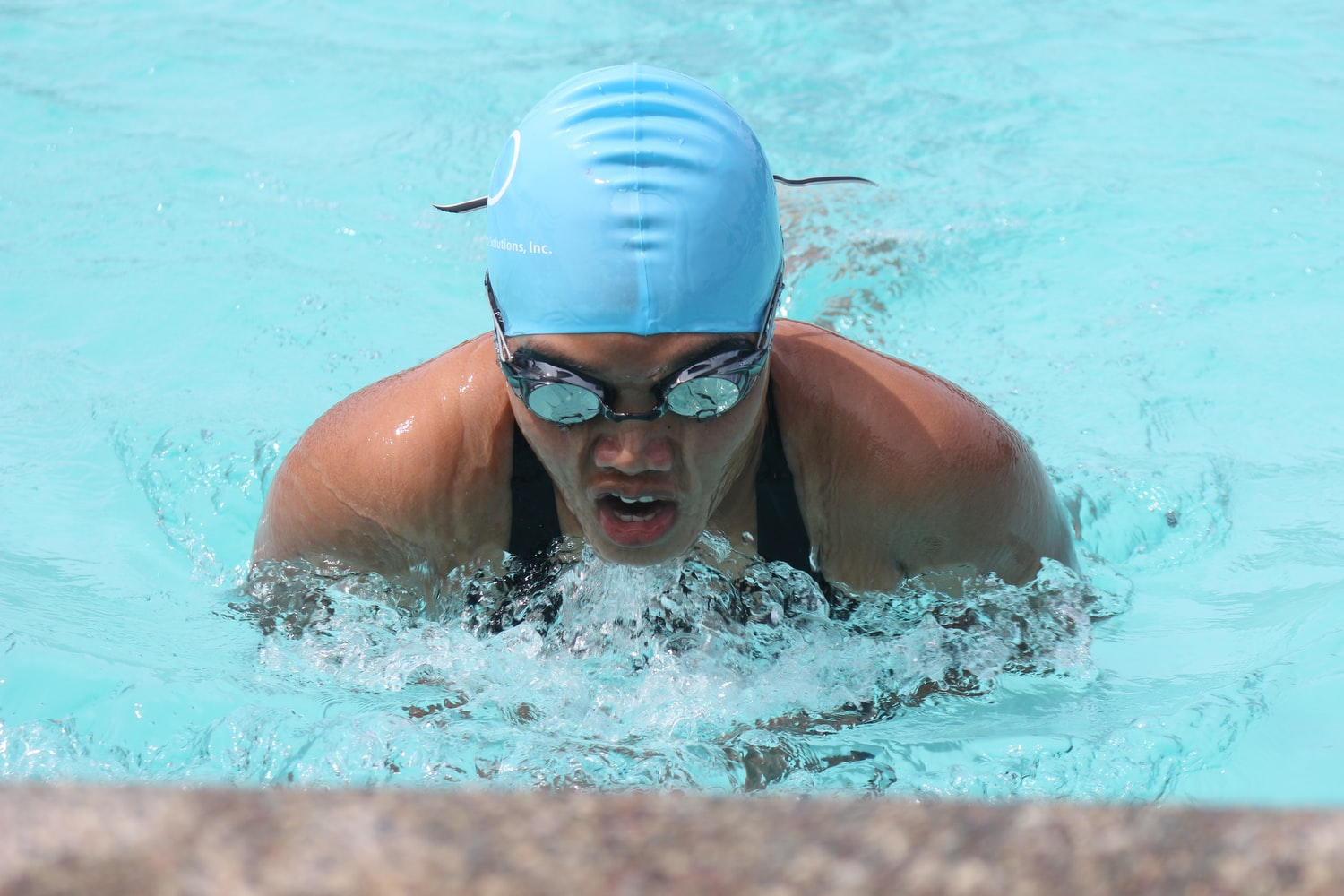 Girl swimmer is wearing a goggles and a swim cap while swimming at the pool