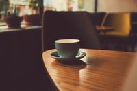 shallow focus photography of teacup with saucer on top of wooden table