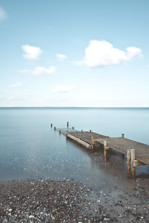 brown metal dock near sea under cloudy sky