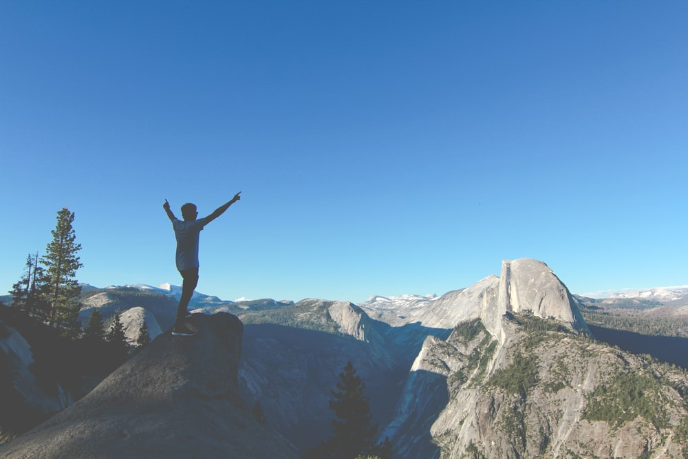 person standing on rock hands up