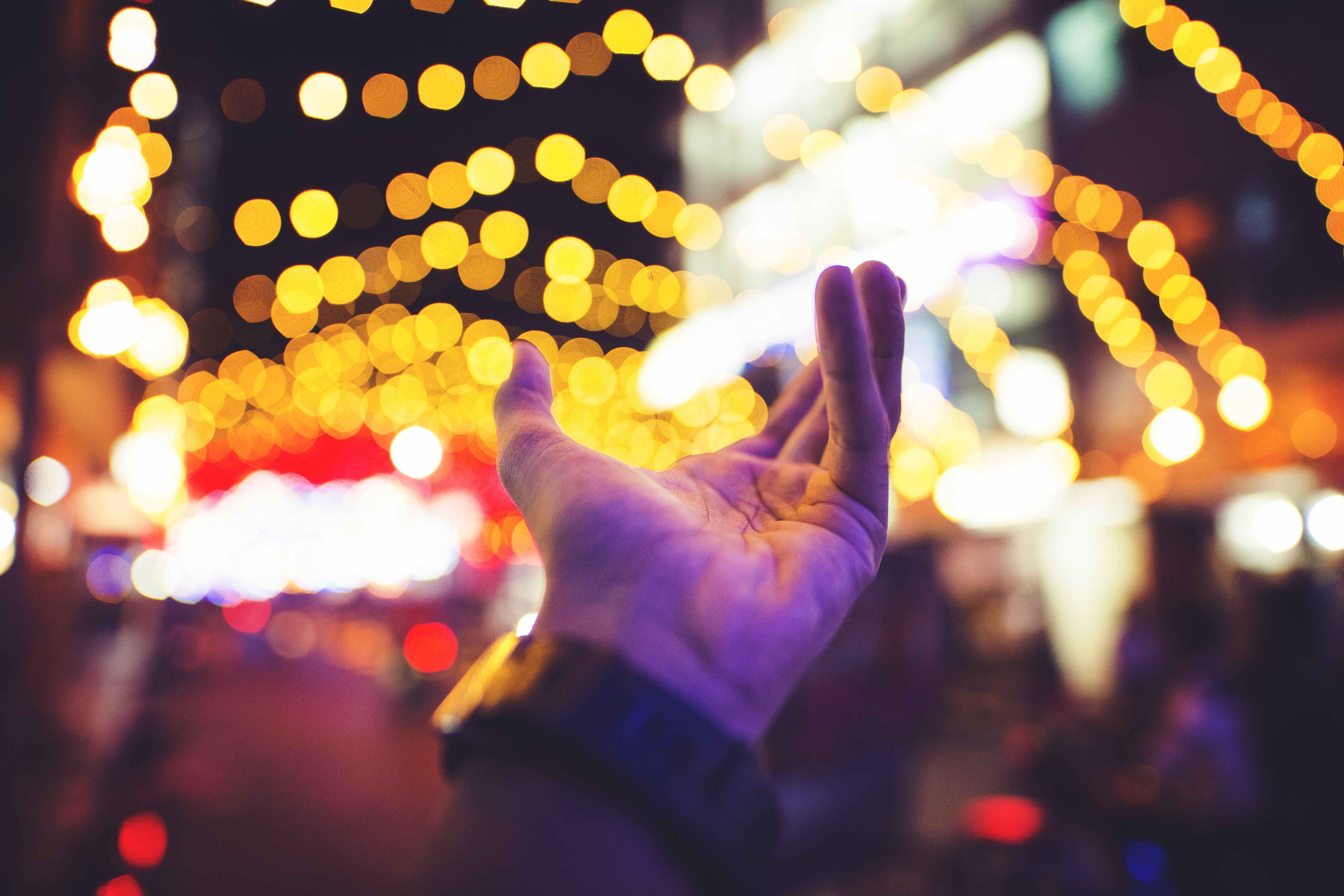 selective focus photography of person's left hand with yellow bokeh light background