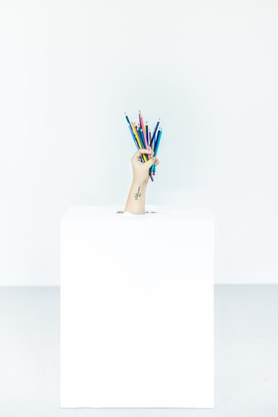 person's hand burst out of box holding assorted-color pens