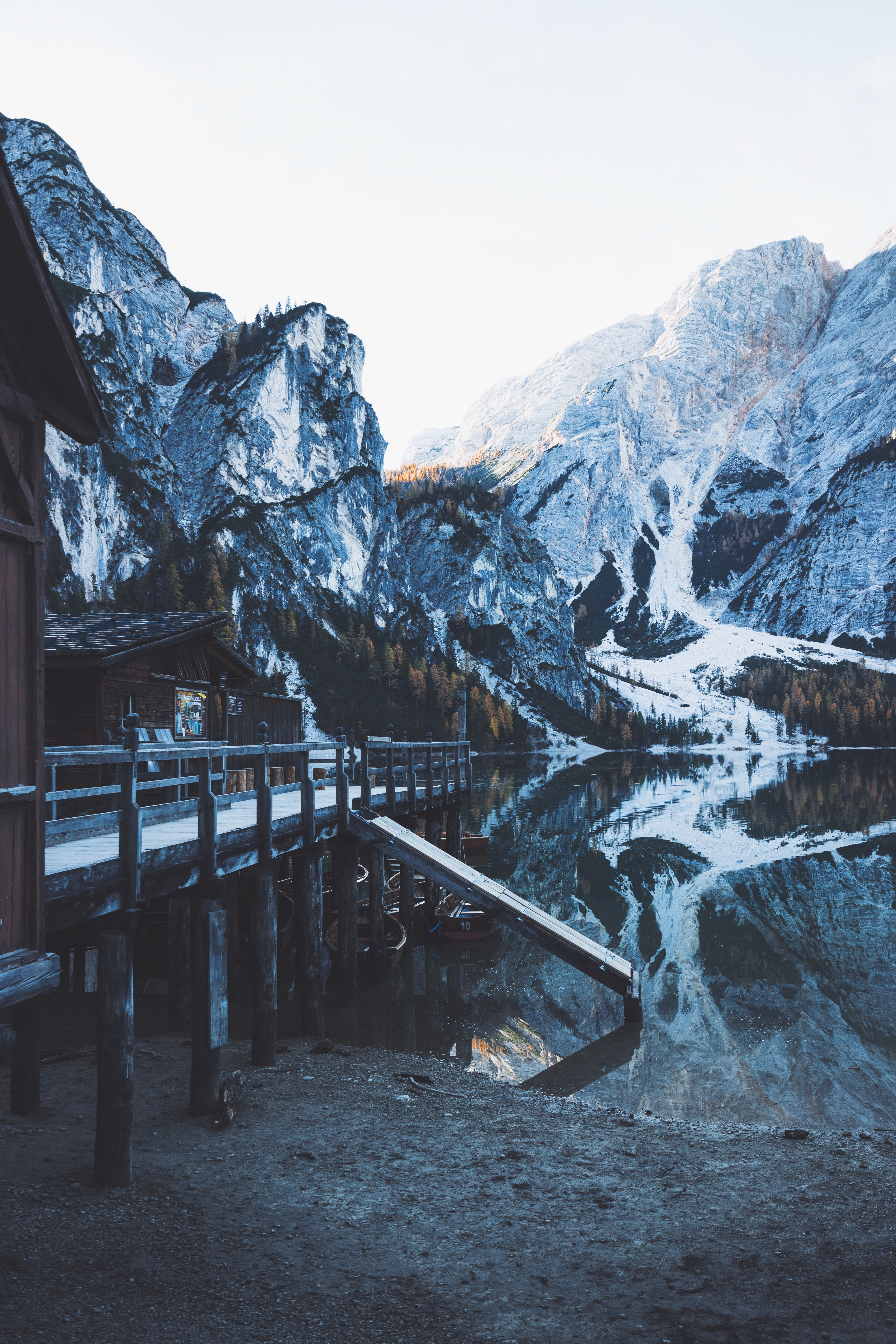brown wooden bridge near river and snow-capped mountains at daytime