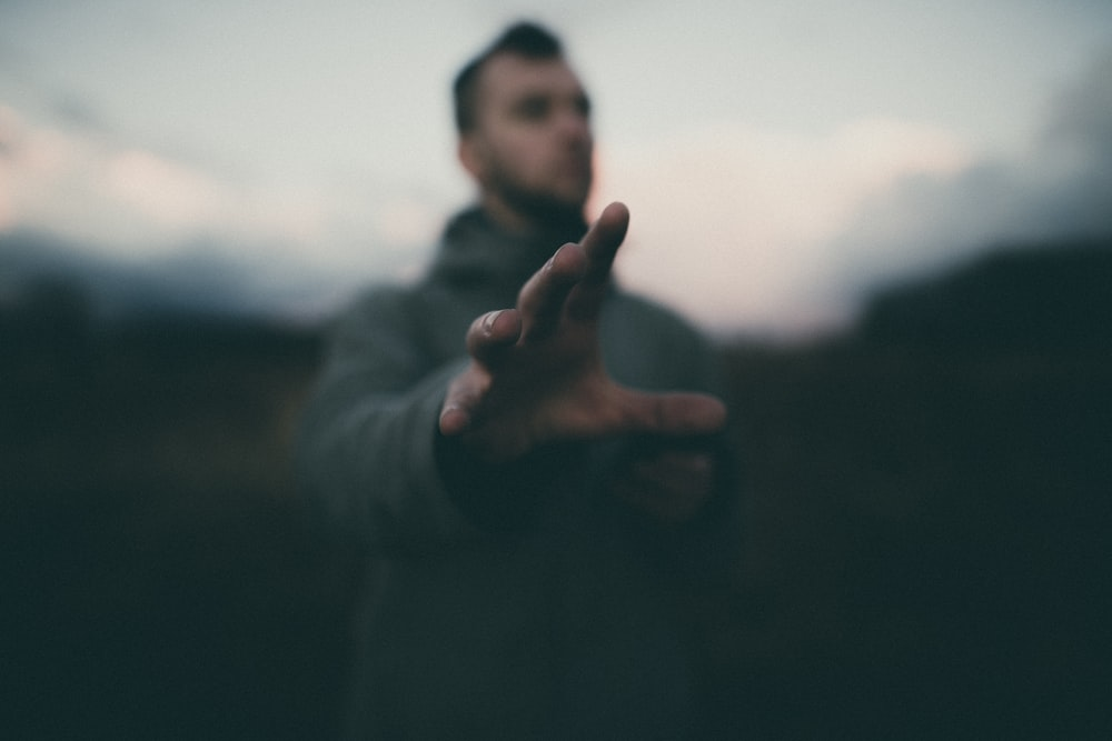 man in gray jacket raising his hand