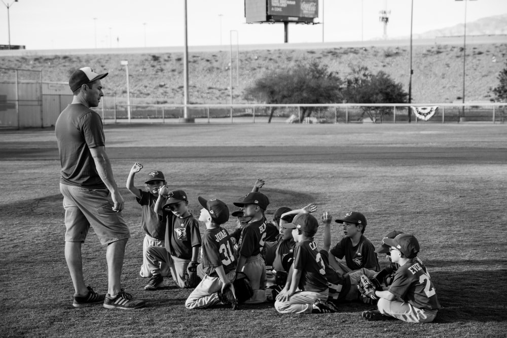 grayscale photo of boys football team in front of coach