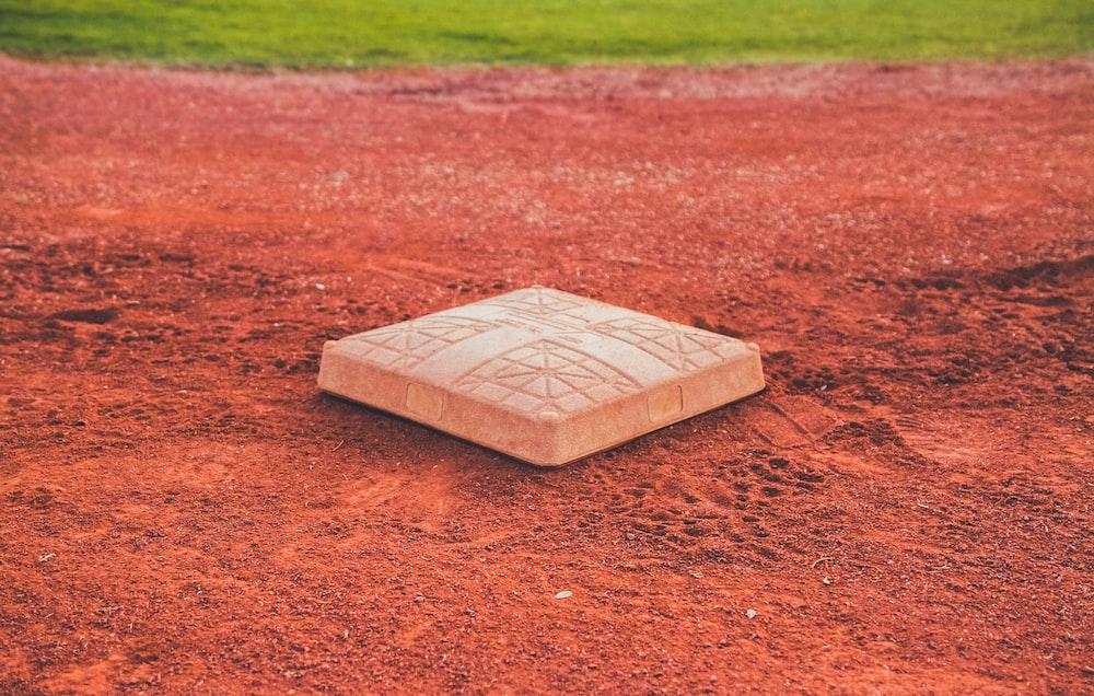 square brown concrete baseball base on soil