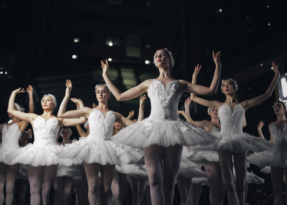 group of ballerinas dancing while raising both hands