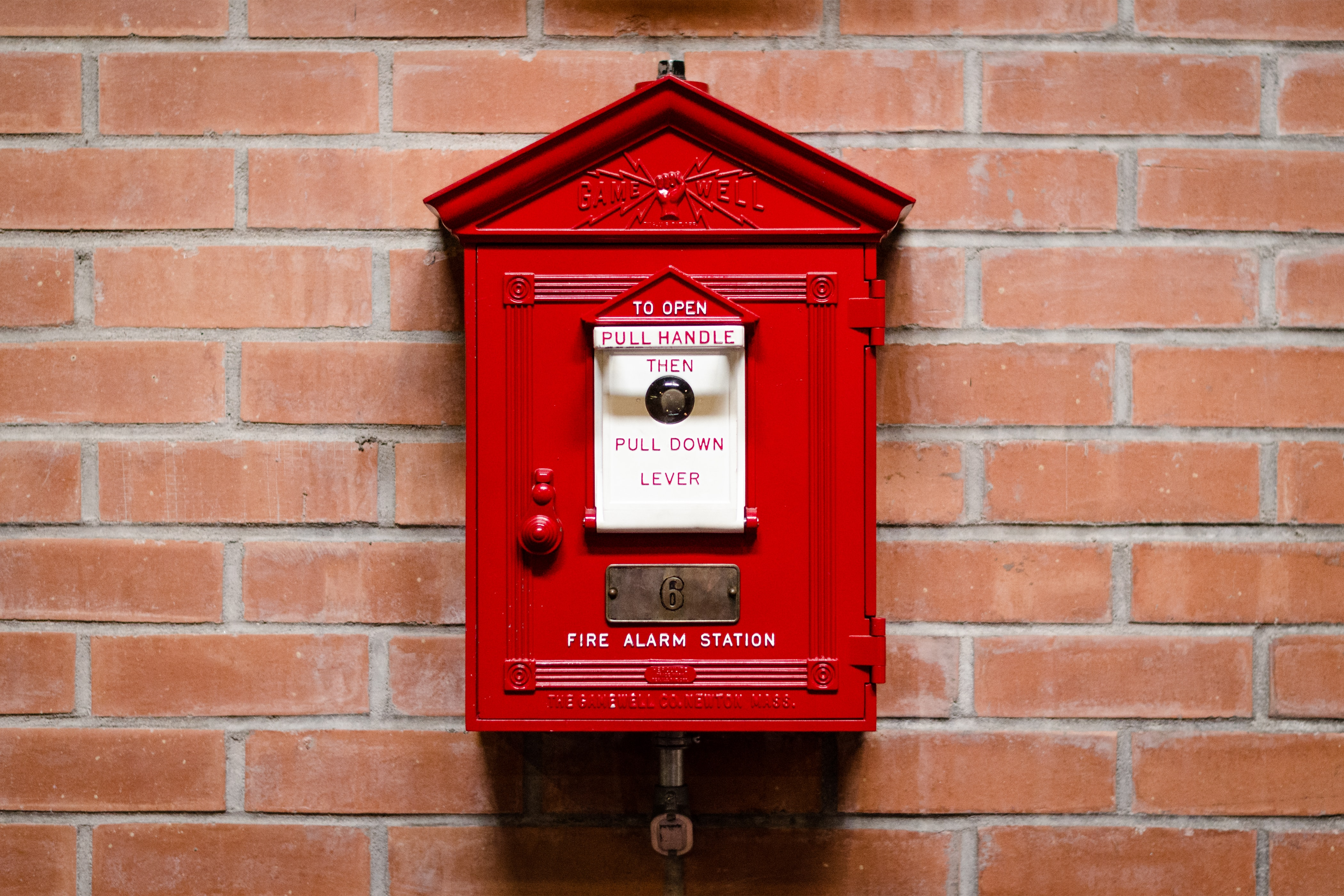 red fire alarm station attached on brick wall