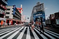 people crossing on pedestrian lane near buildings