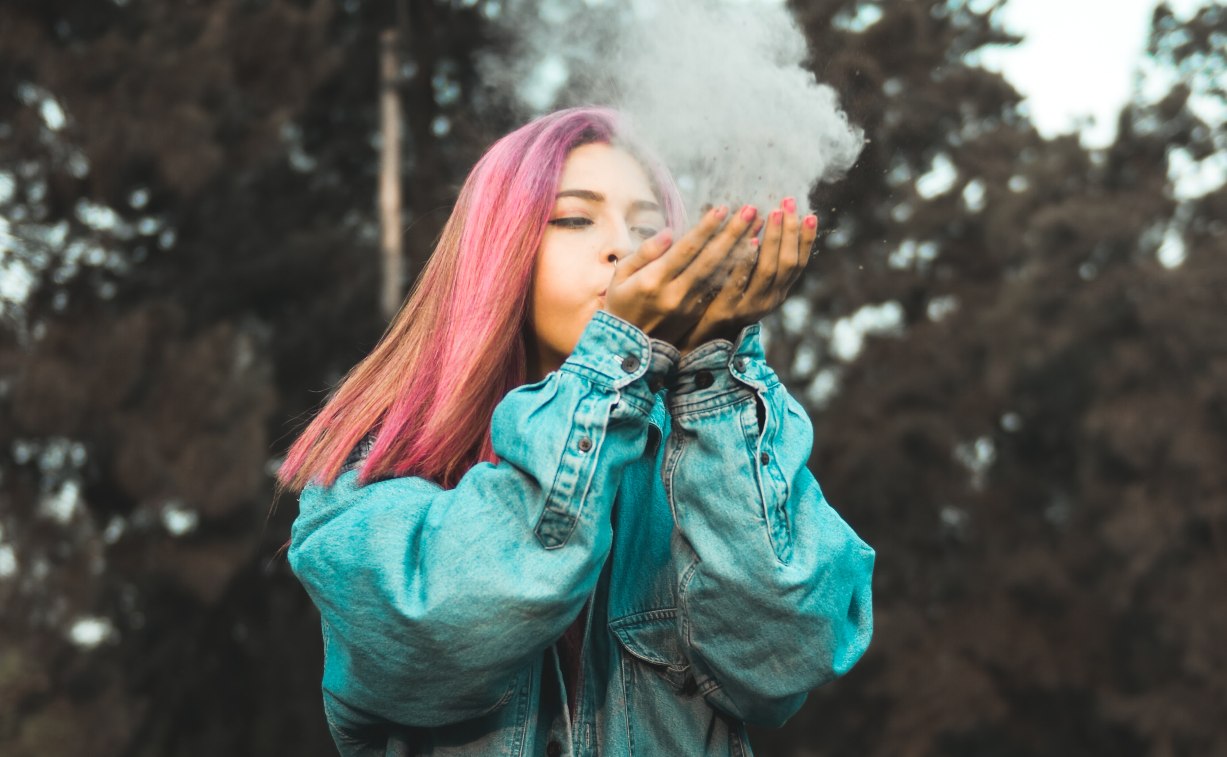 woman blowing powder off her hands