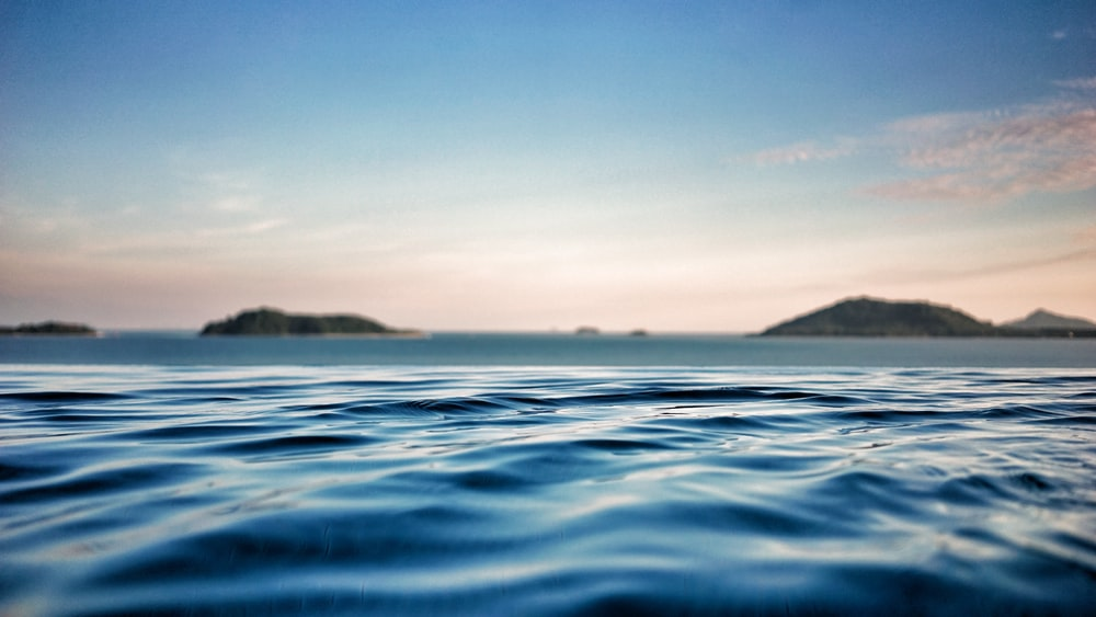 shallow focus photography of ocean with mountain on far side