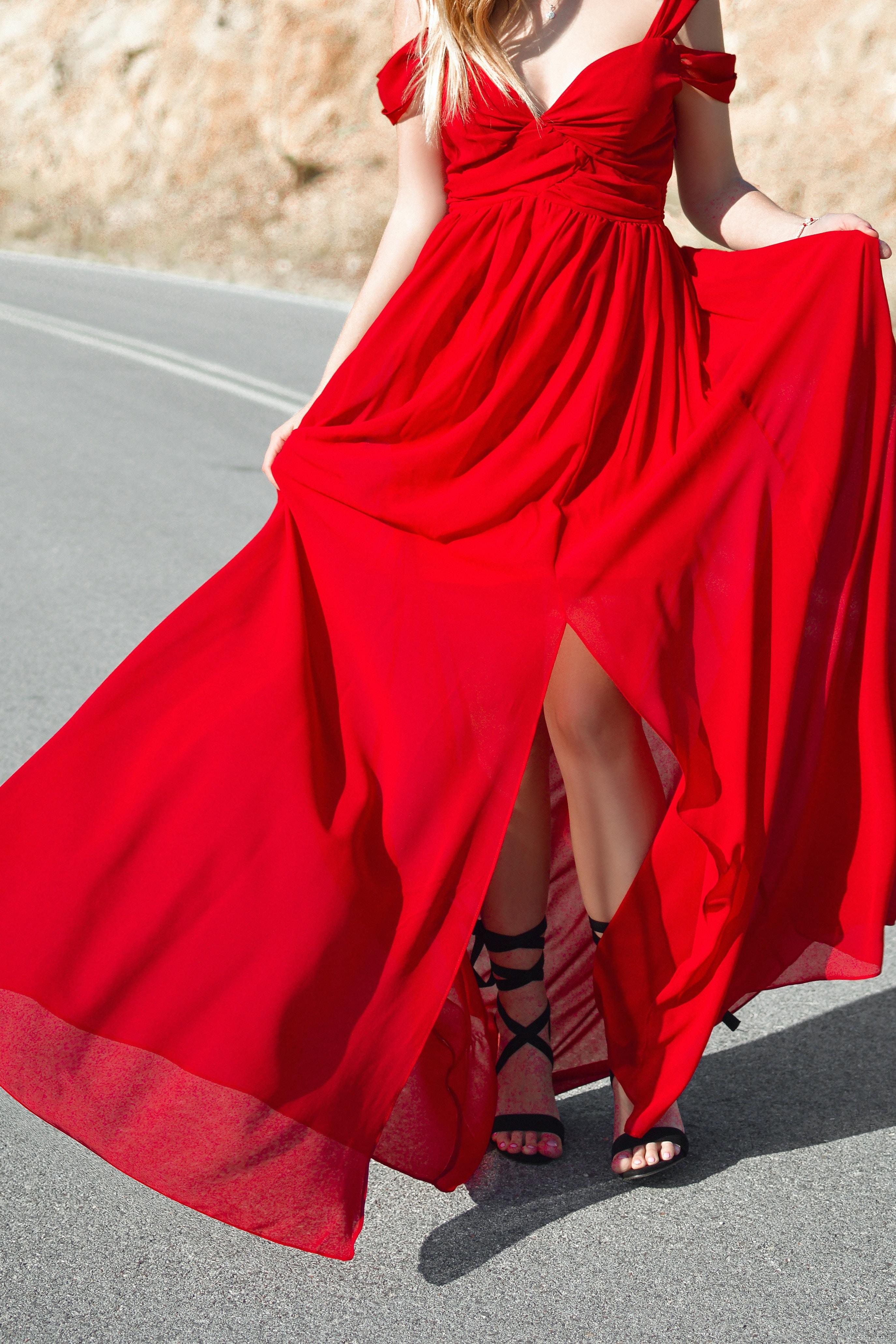 woman wearing red cold-shoulder front-slit formal dress standing on road