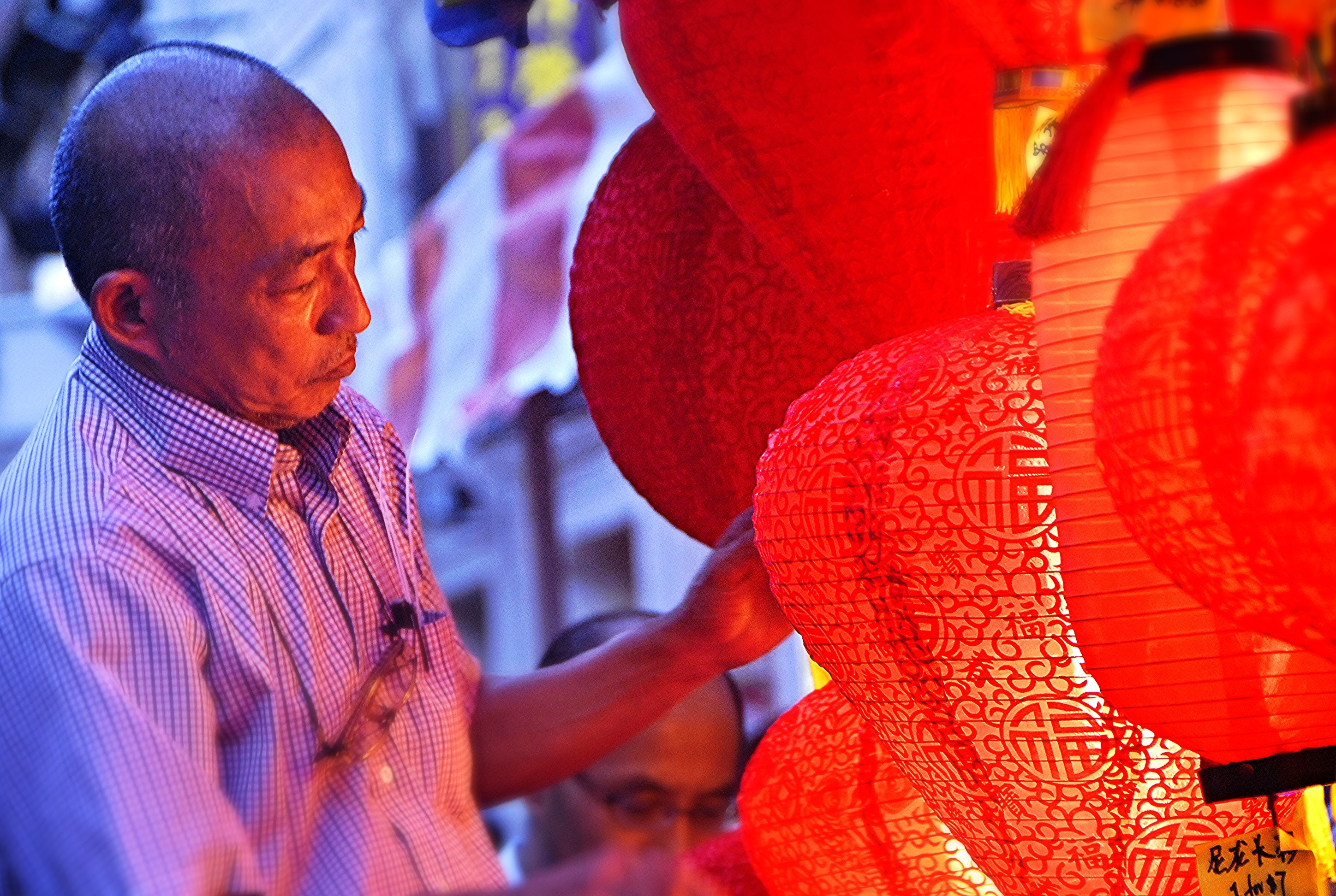 man holding red lanterns at daytime