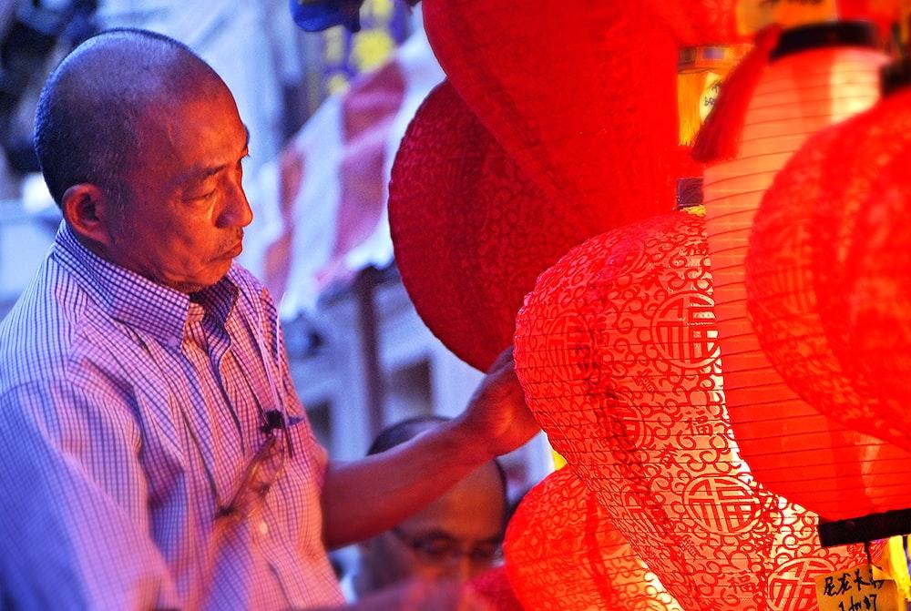man holding red lanterns at daytime