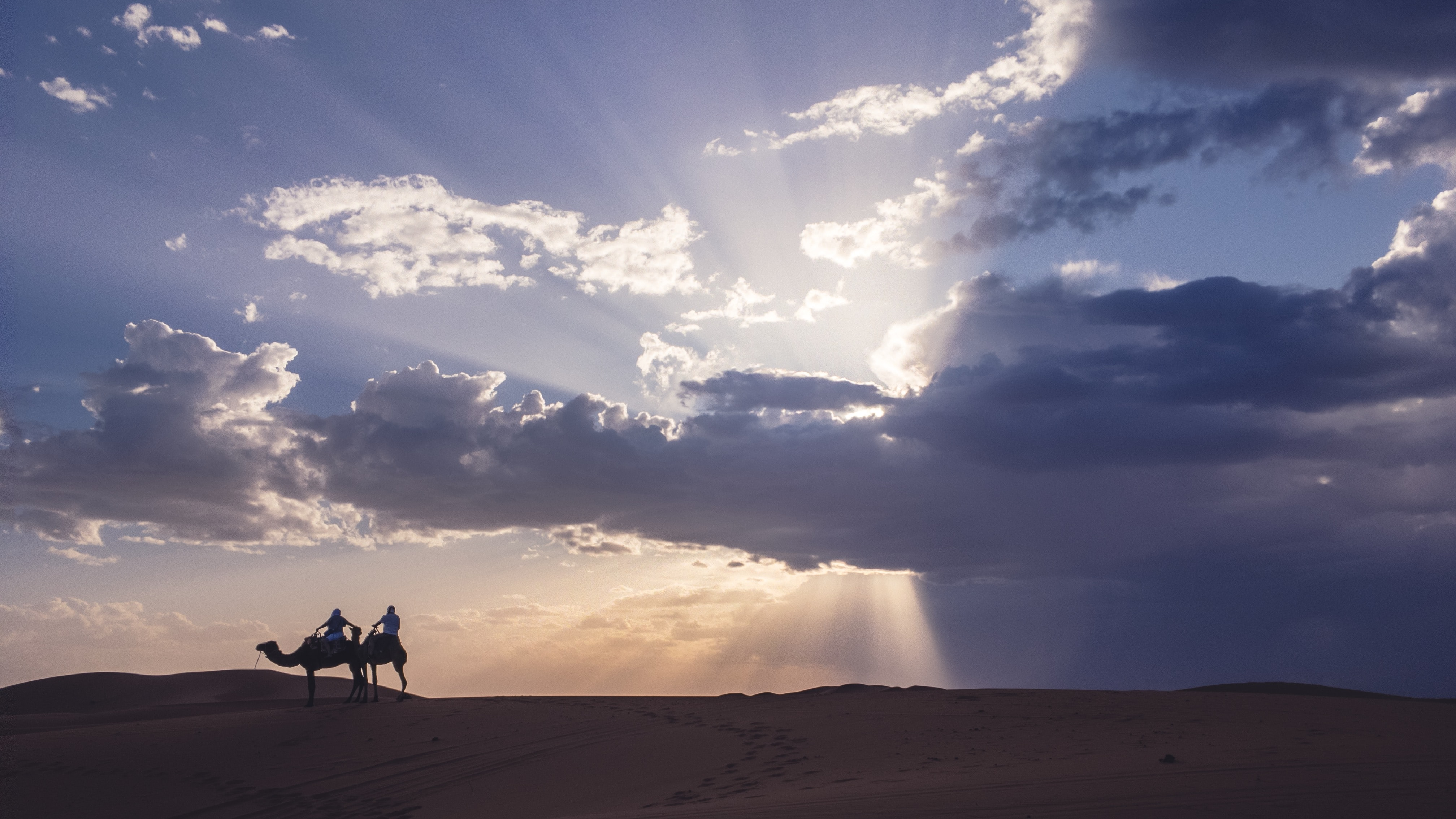 two person riding camel in the sand