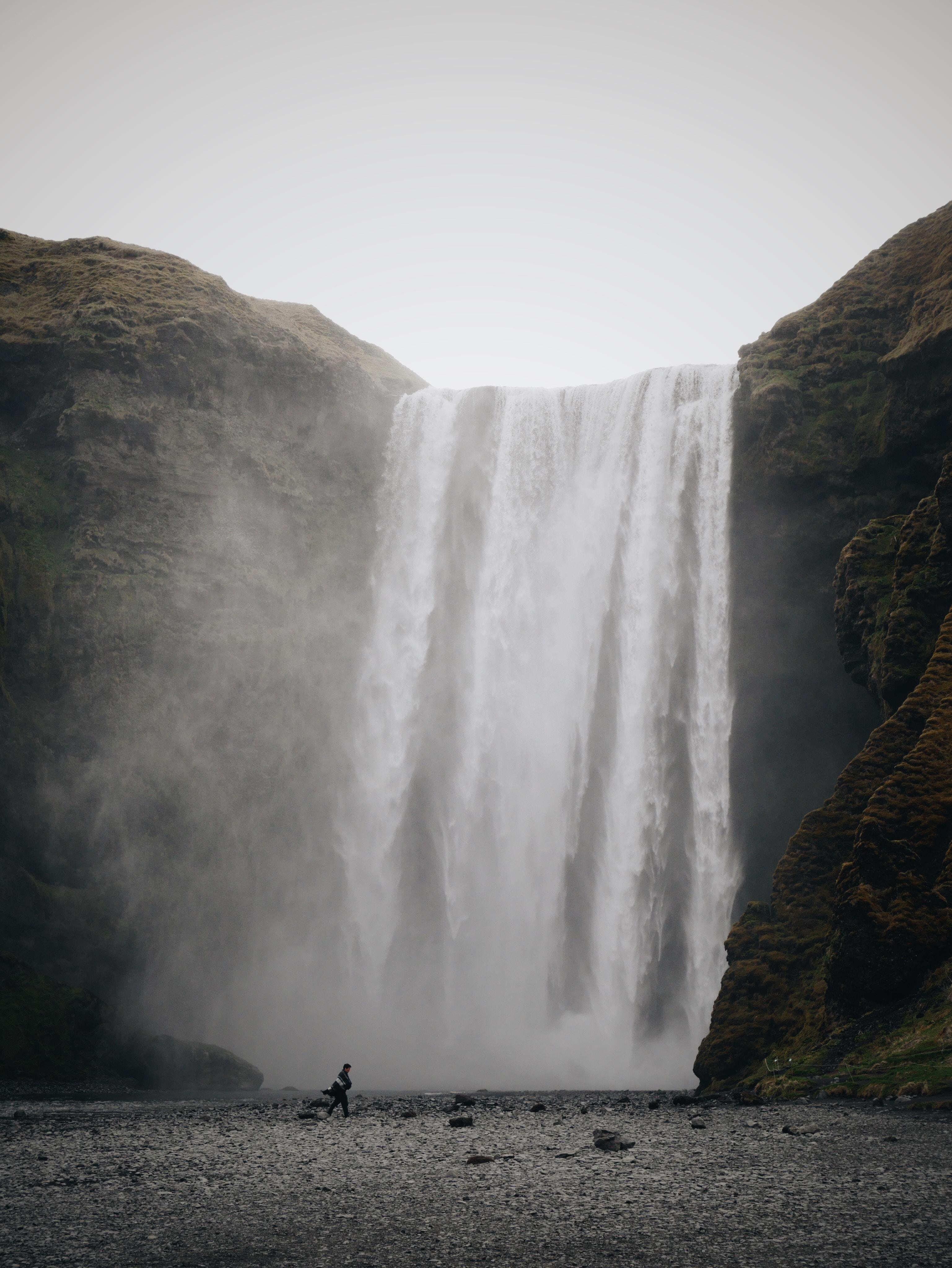 person standing near waterfalls
