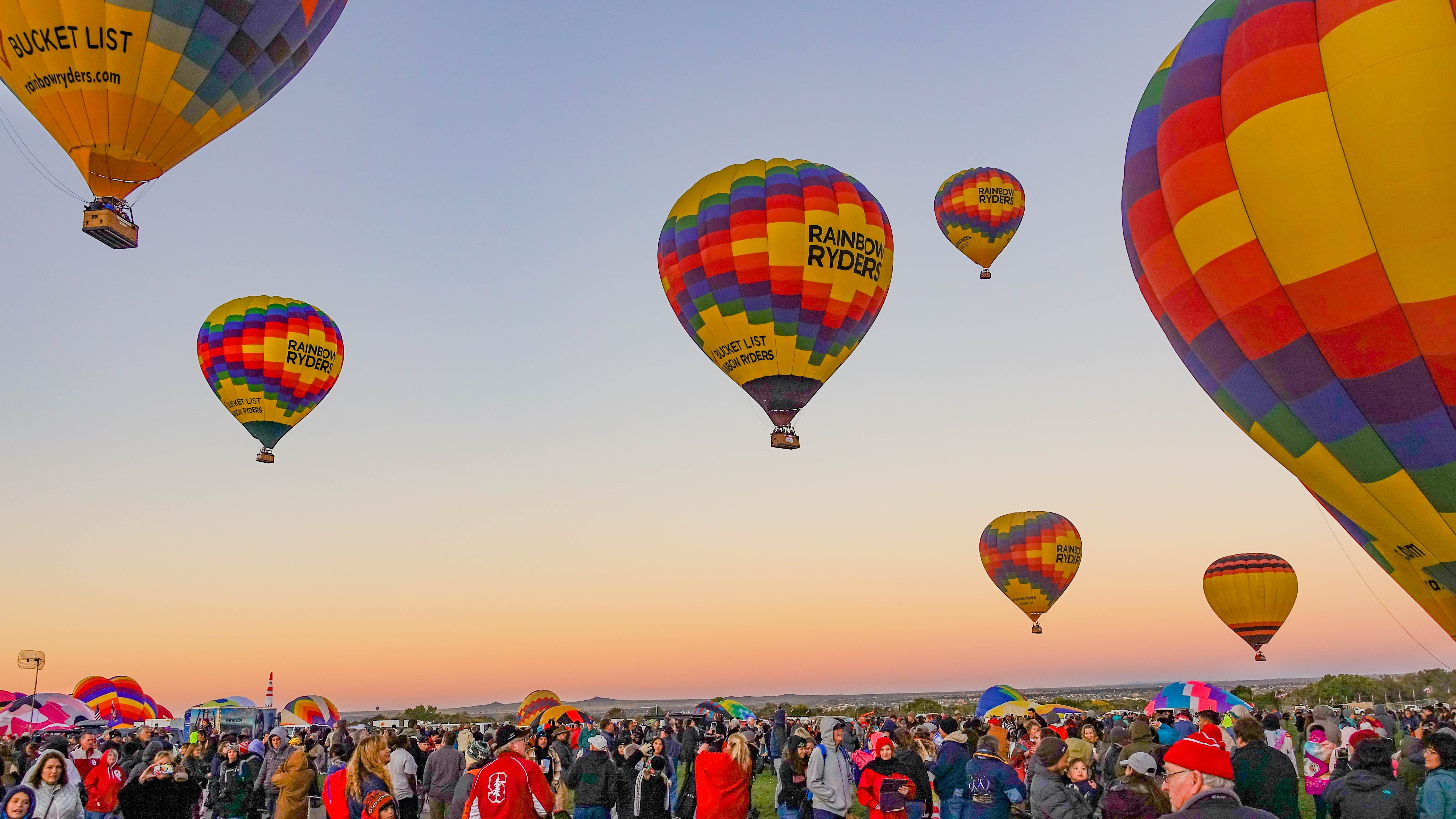 people gathering below multicolored hot air balloons