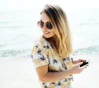 woman standing on shore holding smartphone