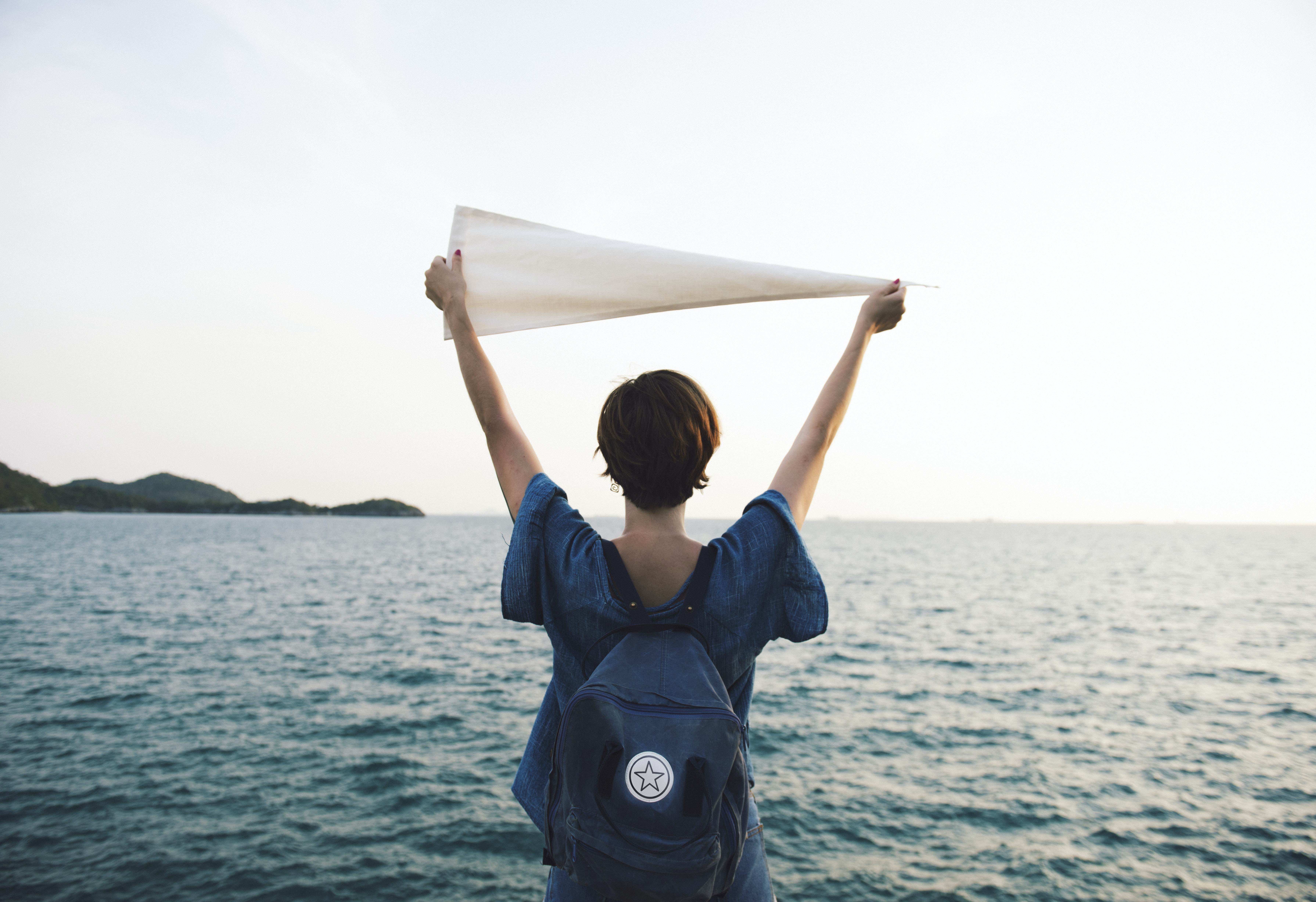 woman holding white pennant in front of body of water