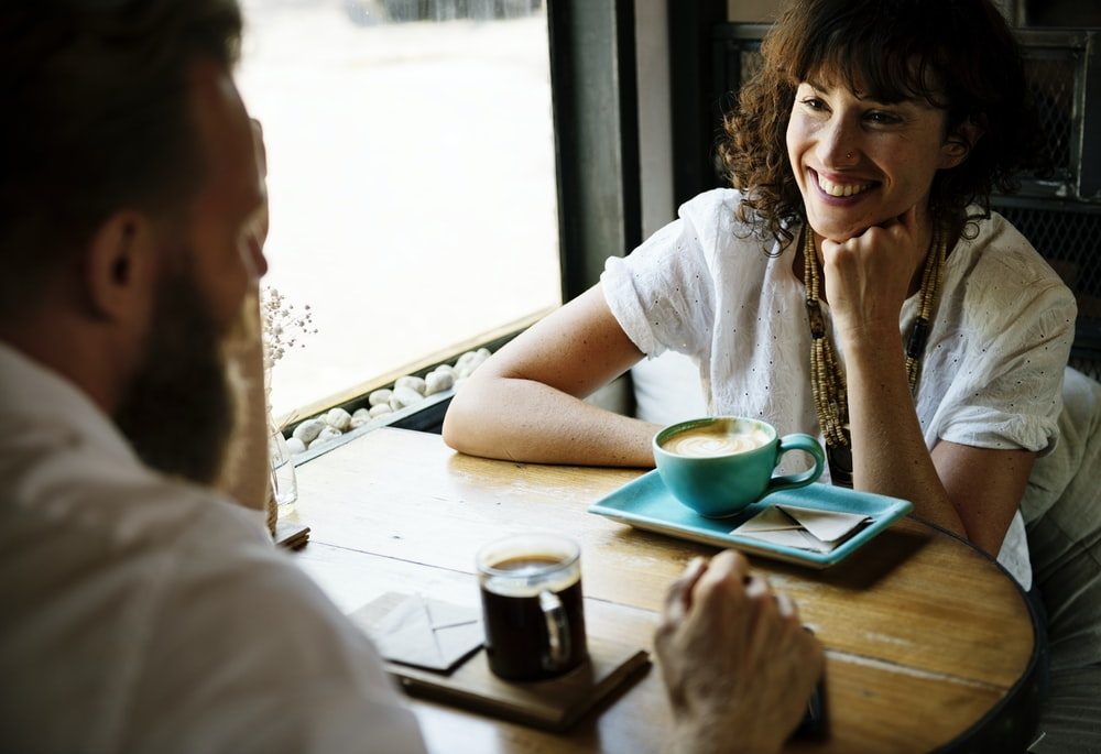 smiling woman sitting front of man near window
