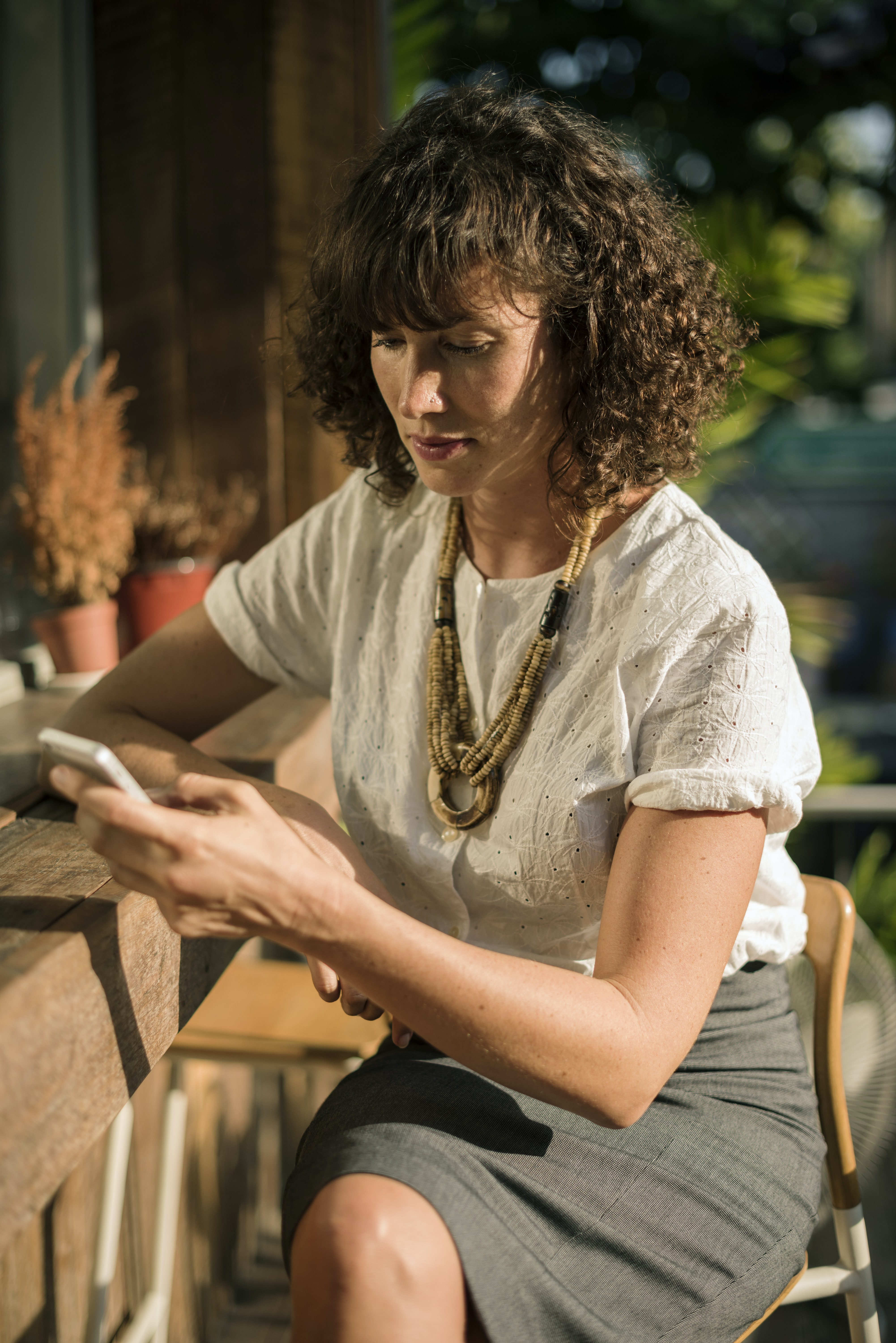 woman in white shirt using smartphone while sitting on bar stool