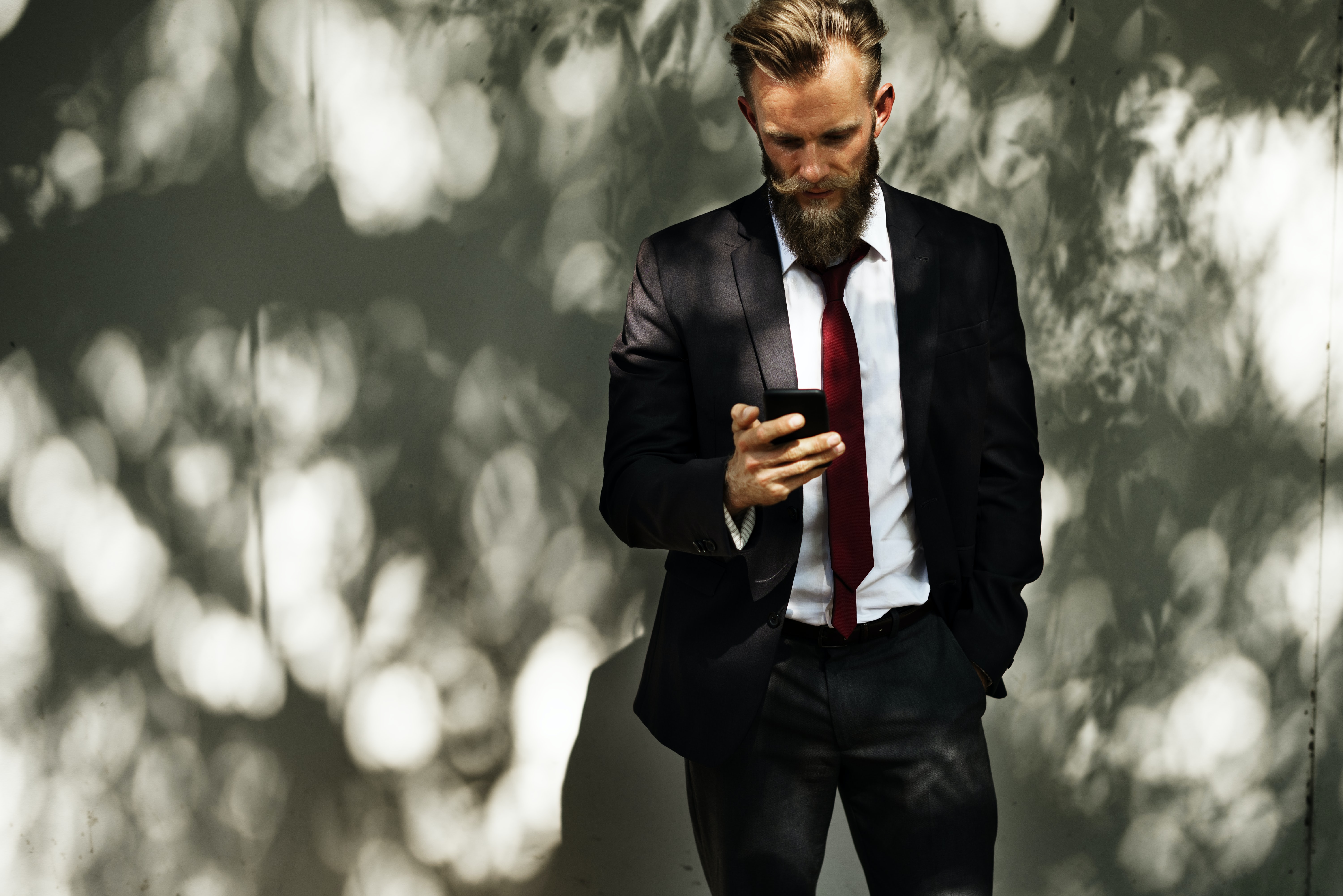 man in suit jacket holding a smartphone