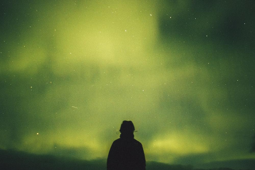 person standing under green aurora borealis