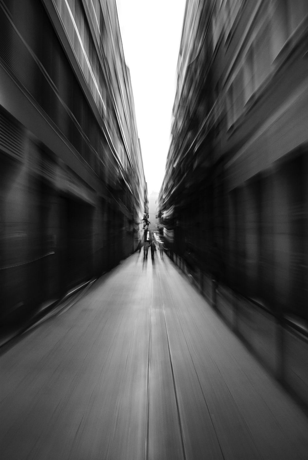 motion photography of person walking between building