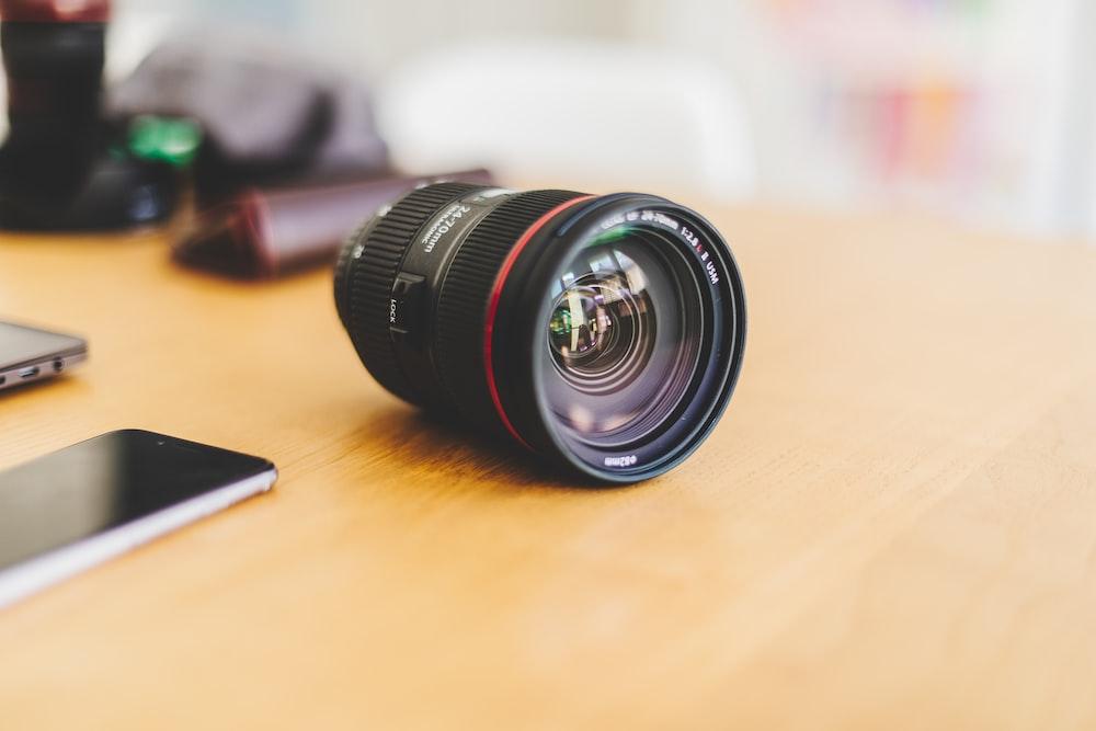 black camera lens on desk beside smartphone
