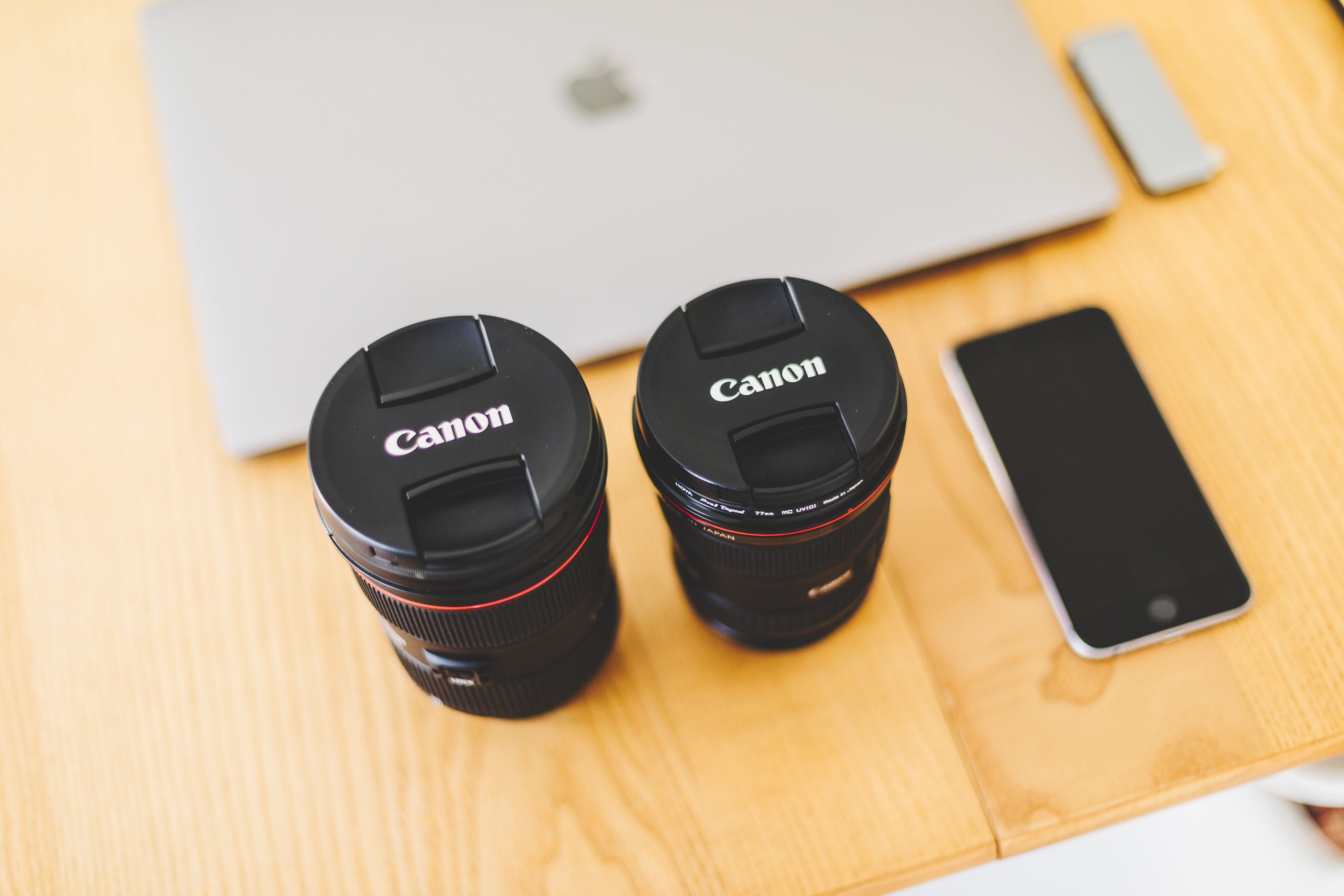 two black Canon camera lens near space gray iPhone 6