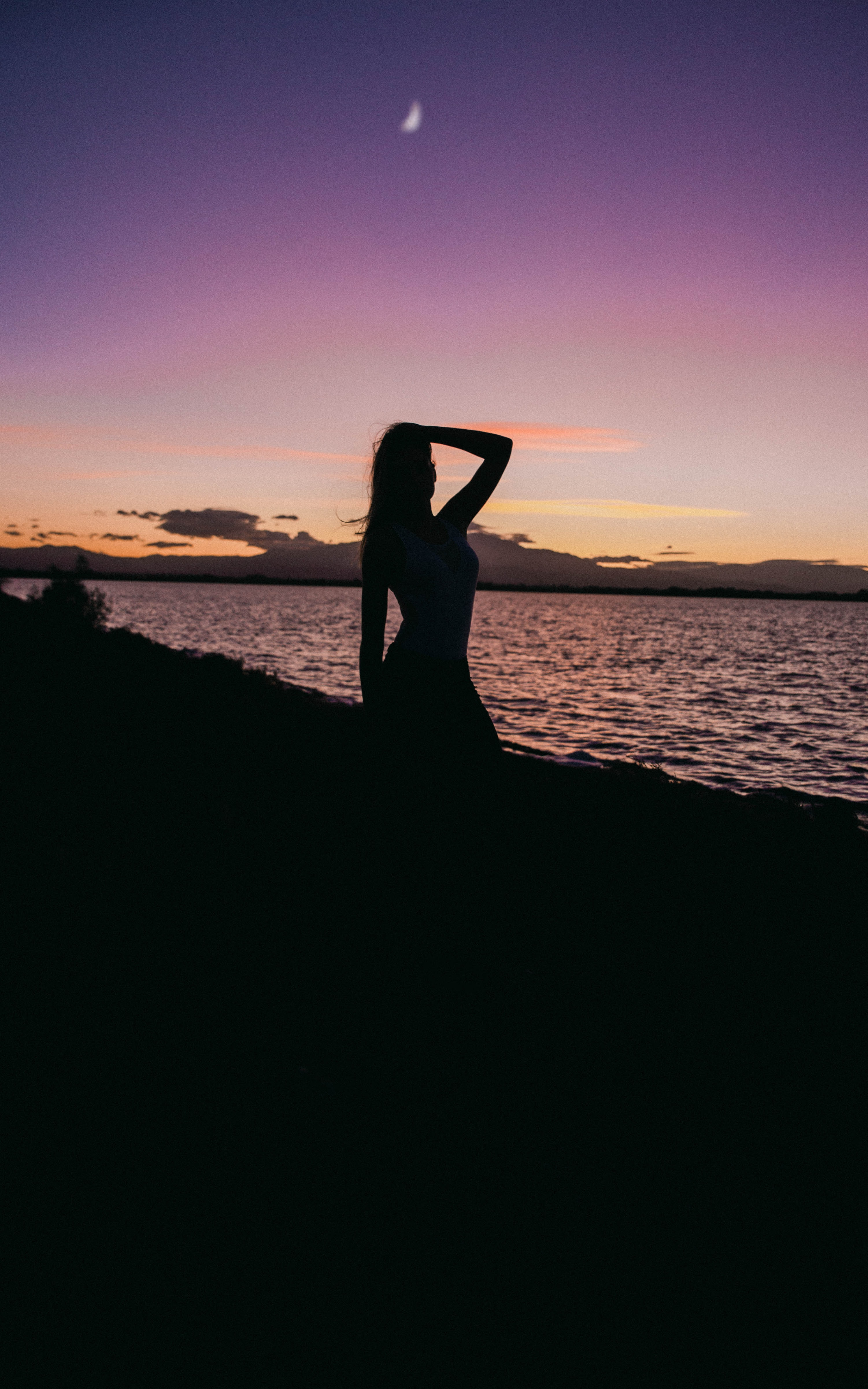 silhouette of woman at beach with left hand on head