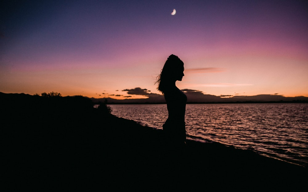 silhouette of woman near of water